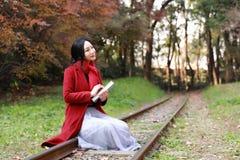 Leggendo in natura è il mio hobby, la ragazza fa il libro e la passeggiata in mezzo alla ferrovia Fotografia Stock Libera da Diritti