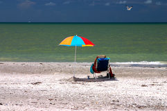Leggendo sotto l'ombrello di spiaggia Immagine Stock Libera da Diritti