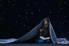 Leggendo sotto la coperta Immagine Stock Libera da Diritti
