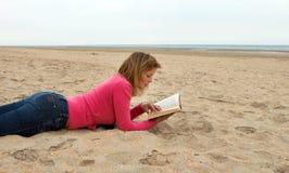 Leggendo su una spiaggia vuota immagine stock