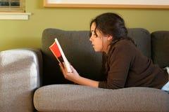 Leggendo sul sofà Immagine Stock Libera da Diritti