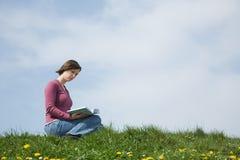 Leggendo un libro all'esterno Immagini Stock