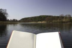 Leggendo un libro su un libro vuoto del lago impagini il modello Immagine Stock