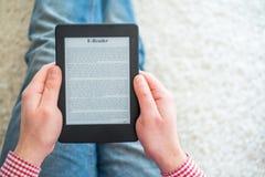 Leggendo un romanzo sul lettore del libro elettronico a casa fotografia stock