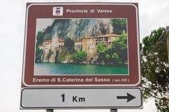 Leggiuno Italien - mars 15, 2017: turist- tecken för eremitboningen av Santa Caterina del Sasso på sjön Maggiore Arkivbild