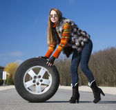 Leggy beautiful female holds big wheel Royalty Free Stock Photos
