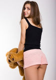 Leggy blonde girl in pink shorts and a short tank top holding a teddy bear Stock Image
