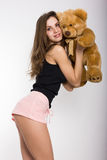 Leggy blonde girl in pink shorts and a short tank top holding a teddy bear Royalty Free Stock Images