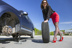 Leggy female changing wheel of car Royalty Free Stock Photos