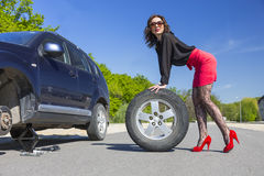 Leggy female changing wheel of car Royalty Free Stock Images