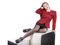 Leggy girl isolated on white. Leggy young pretty woman dressed in red jacket and mini skirt, sitting in studio, looking up, isolated on white background, free Royalty Free Stock Photos