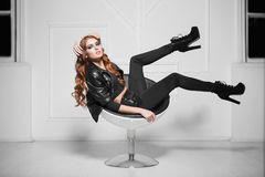 Leggy red-haired lady. Wearing black fashionable clothes posing in a chair Royalty Free Stock Image