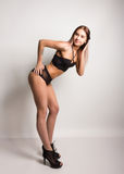 Leggy slim beautiful sexy girl in a bra and black lace panties on a high heels, posing Royalty Free Stock Image