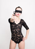 Leggy slim beautiful sexy girl in lacy lingerie on a high heels,  blindfolded, holding a gun in hand, posing Stock Photography