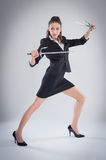 Leggy Woman Posing with Martial Arts Swords. Royalty Free Stock Image