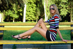 Leggy young blonde. Sitting on a park bench Royalty Free Stock Photography
