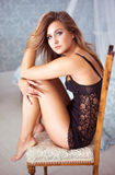 Leggy young woman sitting on a chair Royalty Free Stock Images