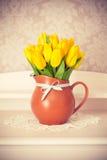 Leghi i tulipani gialli in brocca sulla tavola di legno Fotografia Stock