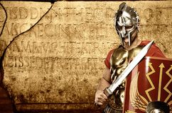 Legionary soldier in front of abstract wall. Roman legionary soldier in front of abstract wall royalty free stock photo