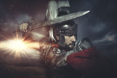 Legionary warrior helmet, armor and red cape on a battlefield, c Royalty Free Stock Photography