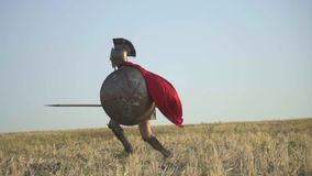 The legionnaire makes a false lance and hits the opponent with a shield. The battle of two roman warriors in armor with shields on the spears in the field on a stock video
