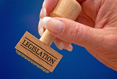 Legislation hand stamp. Woman's hand holding wooden stamp with text legislation on blue background stock photography