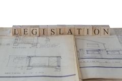 Legislation written on wooden blocks on house extension building plans blueprints. With a white background royalty free stock photos