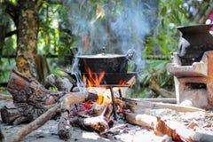 Legna da ardere bruciante nel camino con il vecchio vaso di cottura nero Immagine Stock Libera da Diritti