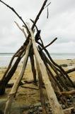 Legname galleggiante impilato in un tepee su una spiaggia abbandonata Fotografie Stock