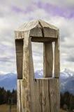 Legname grezzo del totem non dipinto con neve e le montagne sui precedenti Fotografie Stock