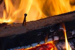 Legno bruciante con il chiodo fotografie stock