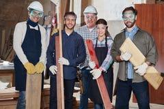 Legno della tenuta del gruppo dei carpentieri Fotografie Stock