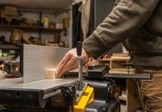 Legno di piallatura dell'artigiano su un jointer fotografie stock