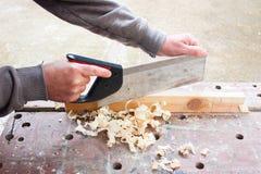 Legno di sawing del carpentiere Fotografia Stock