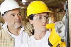 Legno di taglio della lavoratrice con una sega elettrica mentre lavoratore maschio che sta dietro Fotografie Stock