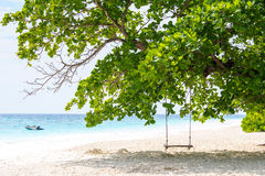 Legno ed abito piacevoli dell'oscillazione sotto il grande albero sulla spiaggia di sabbia con la barca ed il cielo blu nel fondo Fotografia Stock