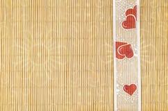 Legno, fondo di vimini con il motivo del fiore e nastro del cuore Fotografie Stock