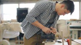 Legno segante del falegname con funzionamento moderno del puzzle nell'officina da solo che fa mobilia stock footage