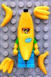Lego Banana Guy-minifigure mit Bananen auf grauem Grundplatte backgr Lizenzfreie Stockfotografie