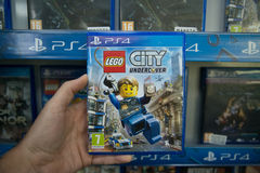Lego city undercover. Bratislava, Slovakia, circa april 2017: Man holding Lego city undercover videogame on Sony Playstation 4 console in store Royalty Free Stock Photo