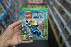 Lego City Undercover videogame on XBOX One. Bratislava, Slovakia, circa april 2017: Man holding Lego City Undercover videogame on Microsoft XBOX One console in Royalty Free Stock Photos