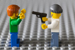 Lego criminal is robbing a Lego citizen.. Royalty Free Stock Images