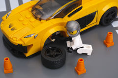 Lego driver is fixing wheel of McLaren P1 by Lego Speed Champion Stock Photos