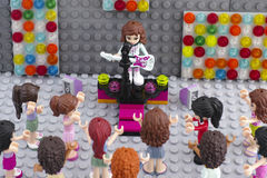 Lego friends concert. Tambov, Russian Federation - August 29, 2015 Lego friends girl minifigure with electric guitar on the stage with microphone is singing song Royalty Free Stock Photos