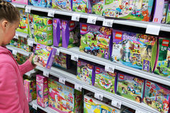 Lego Friends. MALMEDY, BELGIUM - JULY 27  Girl select Lego in toy section of a Carrefour Hypermarket. Lego is a popular line of construction toys manufactured by Stock Image