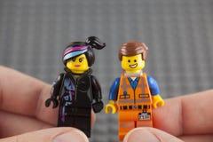 LEGO Hard Hat Emmet och Wyldstyle minifigures i mänskliga händer royaltyfri bild