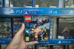 Lego Hobbit. Bratislava, Slovakia, circa april 2017: Man holding Lego Hobbit videogame on Sony Playstation 4 console in store Royalty Free Stock Image
