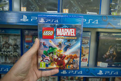 Lego marvel super heroes. Bratislava, Slovakia, circa april 2017: Man holding Lego marvel super heroes videogame on Sony Playstation 4 console in store royalty free stock photo