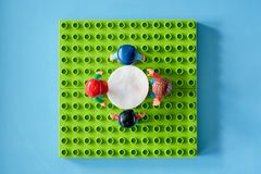 Lego people around the table, combine from different set royalty free stock photo