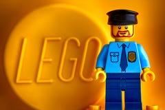 Lego-Polizist minifigure gegen gelben Hintergrund mit Wort Le Lizenzfreie Stockfotos